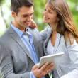 Couple standing in park with electronic tablet — Stock Photo #13935324