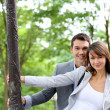 Portrait of cheerful couple standing by lamppost in town — Stock Photo #13935447