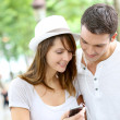 Couple in town using smartphone and handsfree device — Stock Photo