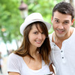 Stock Photo: Couple in town using smartphone and handsfree device