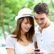 Couple in town using smartphone and handsfree device — Stock Photo #13935512