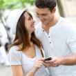 Couple in town using smartphone and handsfree device — Stock Photo #13935518