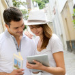 Couple of tourists using guide and tablet in town — Stock Photo