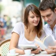 Couple on a coffee shop terrace reading tourist book — Stock Photo #13935570