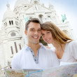 Couple in Montmartre reading tourist map — Stock Photo #13935596