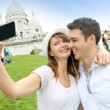 Lovers taking picture of themselves in front of Sacre Coeur — Stock Photo #13935647