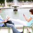Couple relaxing in chairs in public park - Stock Photo