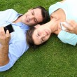 Couple relaxing in grass while using smartphone — Stock Photo