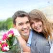 Portrait of romantic man giving flowers to woman — Stock Photo #13935755