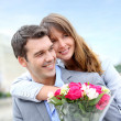Portrait of romantic man giving flowers to woman — Stock Photo