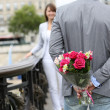 Man ready to give flowers to girlfriend on a bridge — Stock Photo