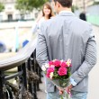 Stock Photo: Man ready to give flowers to girlfriend on a bridge