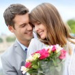 Portrait of romantic man giving flowers to woman — Stock Photo #13935775