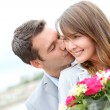 Portrait of romantic man giving flowers to woman — Stock Photo #13935776