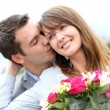 Portrait of romantic man giving flowers to woman — Stock Photo #13935777