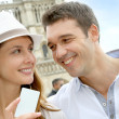 Couple showing tourist pass in front of Notre Dame - Stock Photo