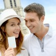 Couple showing tourist pass in front of Notre Dame — Stock Photo