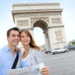 Couple reading map in front of the Arch of Triumph — Stock Photo