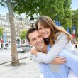 Man giving piggyback ride to girlfriend on the Champs Elysees — Stock Photo #13935806