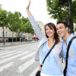 Couple of tourists in Paris calling for a taxi cab - Stock Photo