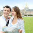 couple reading tourist map in front of the invalides building — Stock Photo