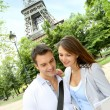 Couple reading tourist map in front of the Eiffel tower — Stock Photo