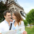 Couple reading tourist map in front of the Eiffel tower — Stock Photo #13935850