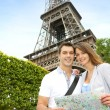 Couple reading tourist map in front of the Eiffel tower — Stock Photo #13935851