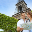 Couple reading tourist map in front of the Eiffel tower — Stock Photo #13935852