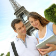 Tourists using electronic tablet in front of the Eiffel tower — Stock Photo
