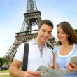 Tourists using electronic tablet in front of the Eiffel tower — Stock Photo #13935875