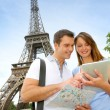 Tourists using electronic tablet in front of the Eiffel tower - Stock Photo