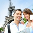 Couple in front of the Eiffel tower holding tourist pass — Stock Photo