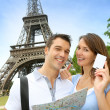 Couple in front of the Eiffel tower holding tourist pass — Stock Photo #13935886