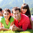 Portrait of happy family laying on the grass in mountain — Stock Photo #13936880