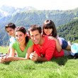 Portrait of happy family laying on the grass in mountain - Foto Stock