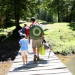 Back view of family walking on a bridge in forest — Stock Photo