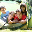 Portrait of family laying in camp tent — Stock Photo #13936915