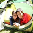 Portrait of cheerful couple relaxing in camp tent — Stock Photo