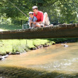Stock Photo: Father fishing with son on a bridge in the mountain