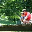 Father fishing with son on a bridge in the mountain — Stock Photo #13936977