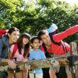 Family on a hiking day resting along fence — Stock Photo #13937027