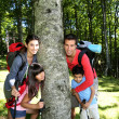 Family leaning on a tree in a middle of forest — Stock Photo #13937034