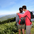 Couple on a trekking day looking at beautiful scenery - Foto Stock