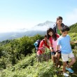Family in a hikking day climbing up the hill — Stock Photo