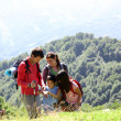 Family on a trekking day looking at wild flowers — Stock Photo