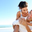 Man carrying girlfriend on his back at the beach — Stock Photo #13937232