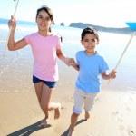 Kids running on the beach with swirls — Stock Photo #13937241