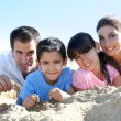 Family of four laying on a sandy beach — Stock Photo