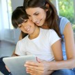 Mother and daughter websurfing on internet with tablet — Stock Photo #13937269